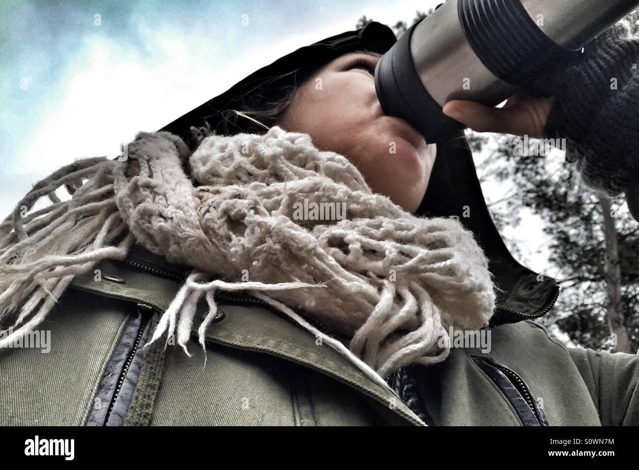 Donna di bere il caffè in una piovosa giornata fredda Immagini Stock