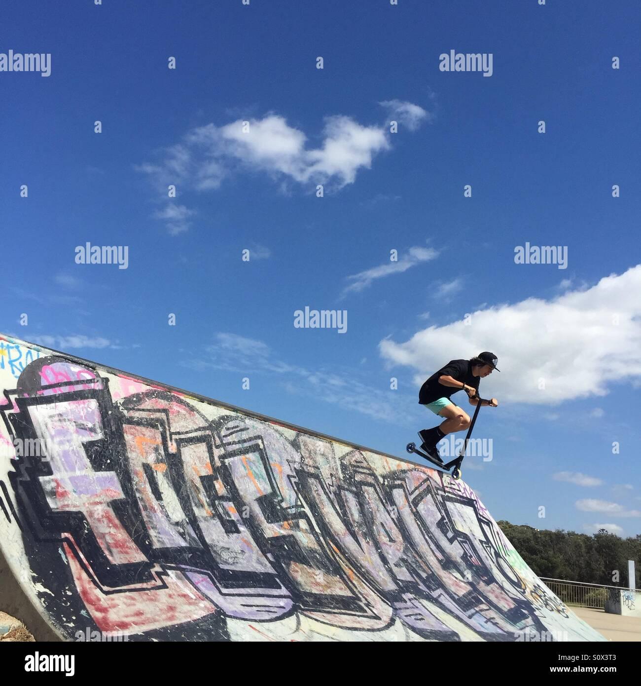 Adolescente scooter di equitazione su skate park Immagini Stock