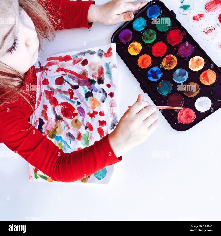 Immagine di una giovane ragazza utilizzando colori di acqua per fare disegni su carta. Immagini Stock