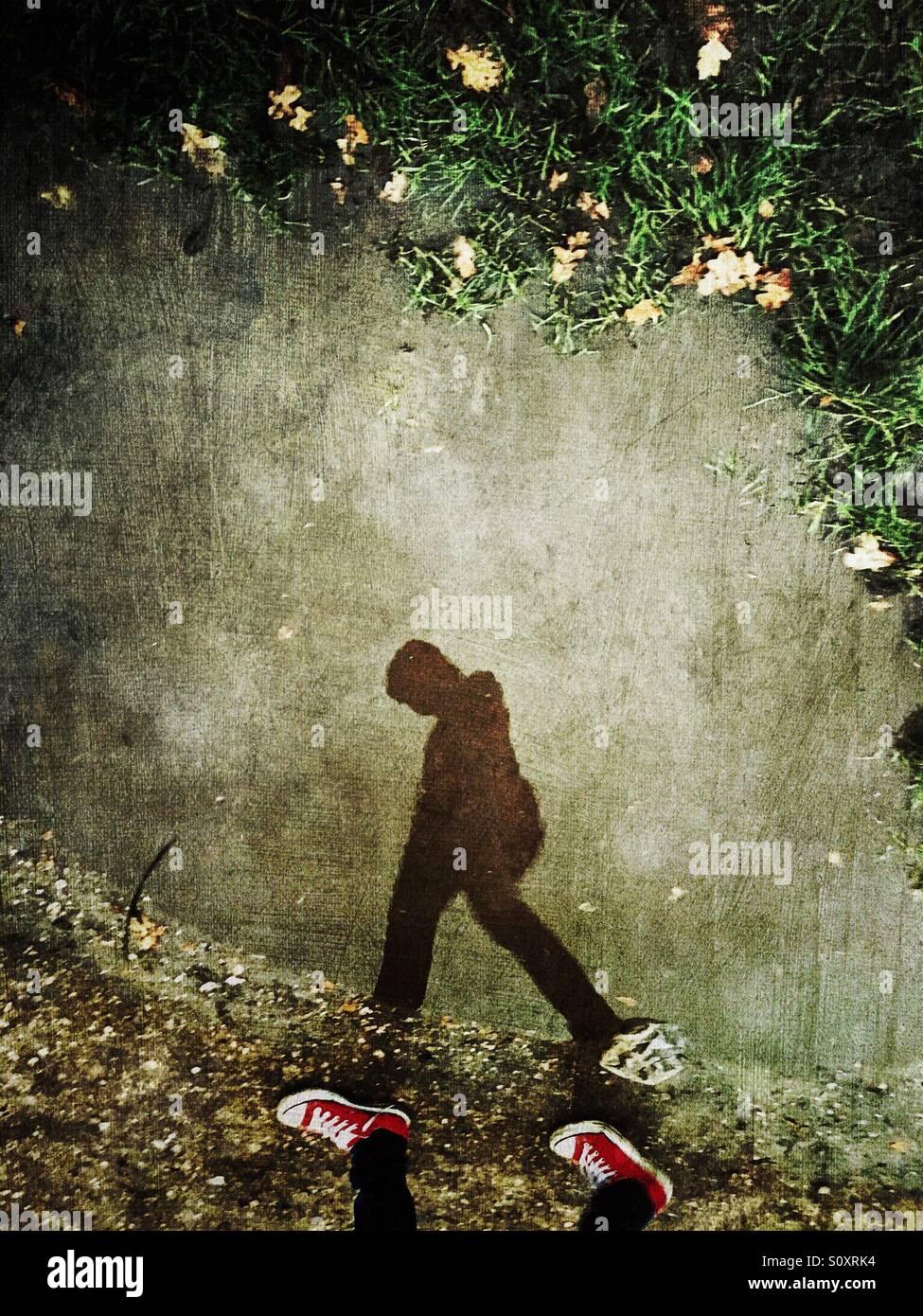 La riflessione di rendere i giovani a camminare con la testa in giù Immagini Stock