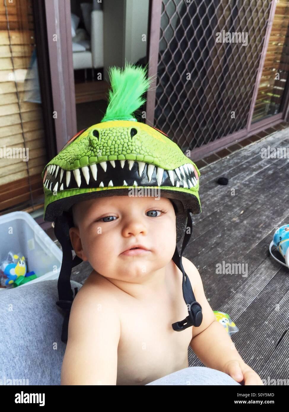 Carino piccolo ragazzo con il suo casco di dinosauri sul Immagini Stock