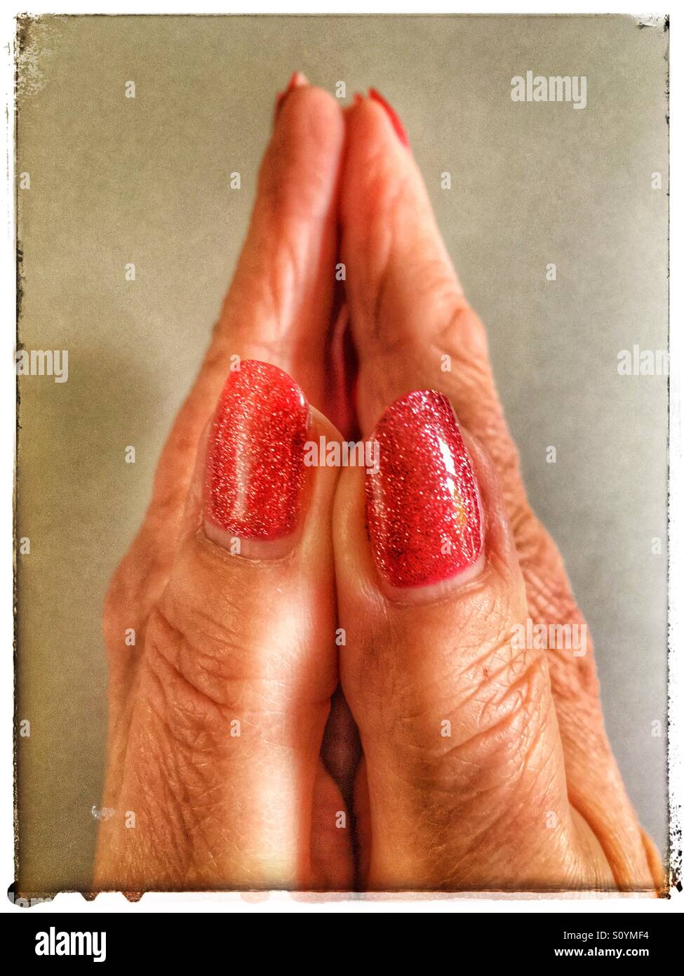 Il disco ha lavorato mani femminili nel pregare posano con scintillanti lucidato rosso unghie Immagini Stock