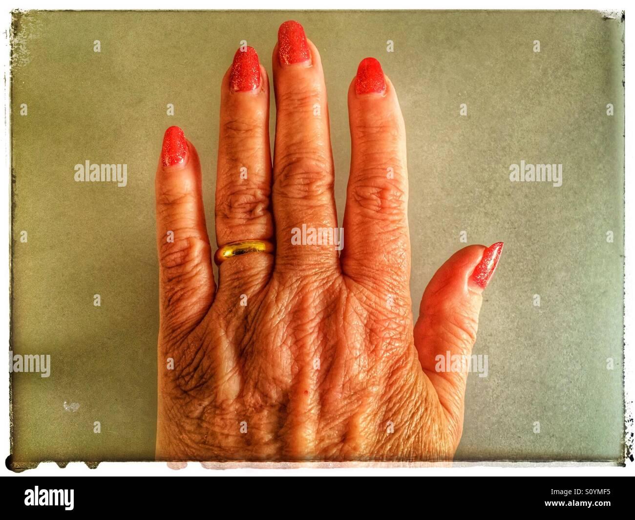 Il disco ha lavorato a mano femmina con vivace rosso smalto per unghie e oro wedding band Immagini Stock