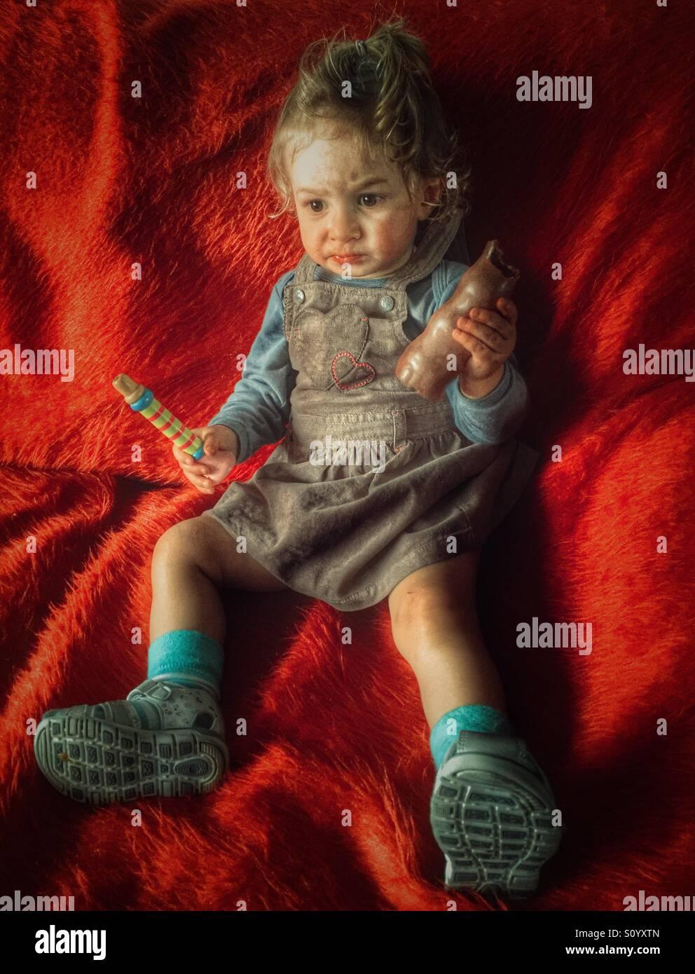 Diciotto mesi baby ragazza seduta sul divano e mangiare il cioccolato Immagini Stock