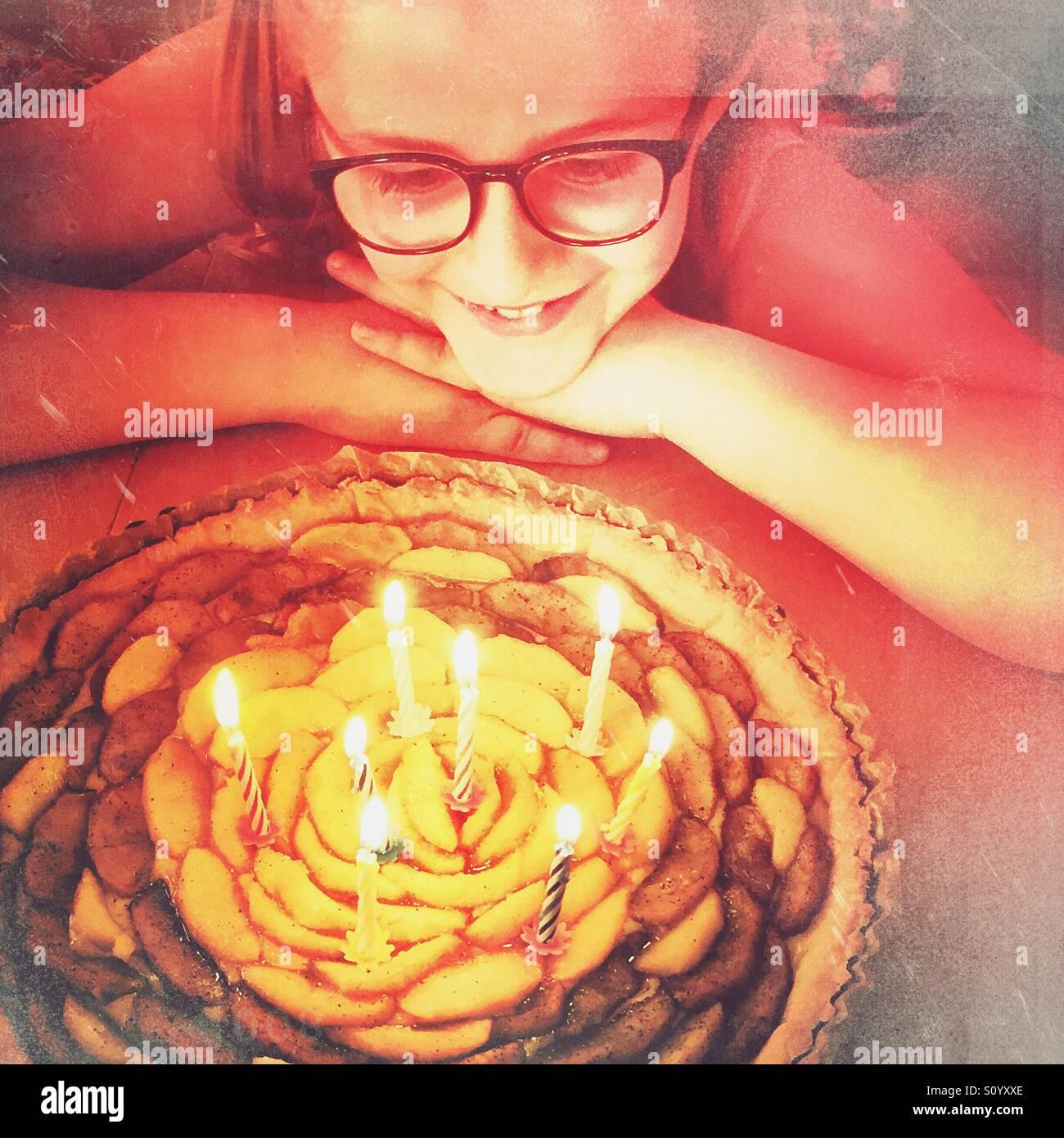 Bambina con occhiali guardando il suo compleanno la torta di mele con 8 candele Immagini Stock