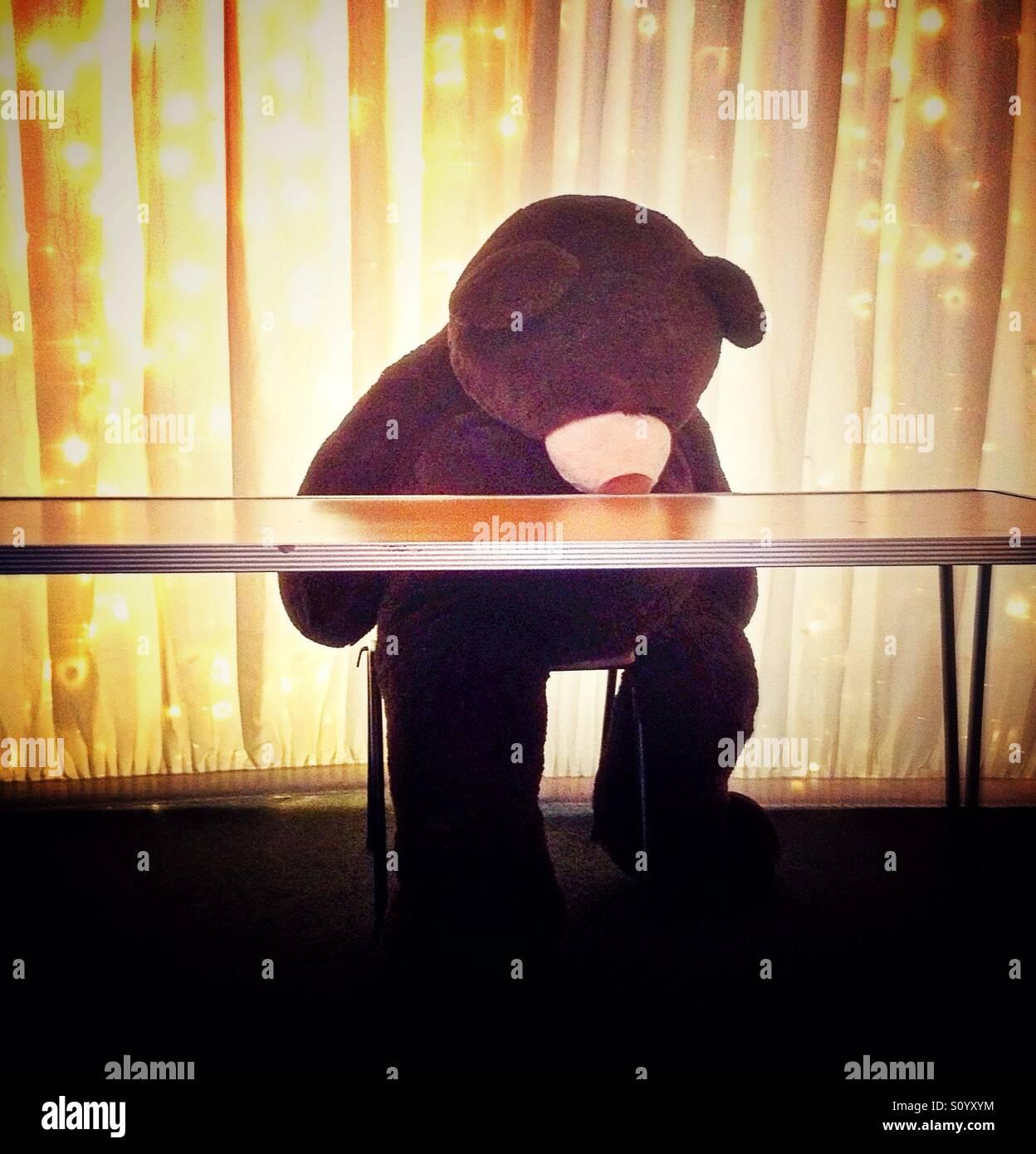 Gigantesco orso di peluche seduta a tavola cercando solitaria e triste Immagini Stock