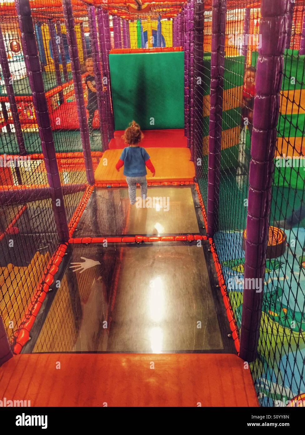 Bambino a giocare nel parco giochi al coperto m Immagini Stock