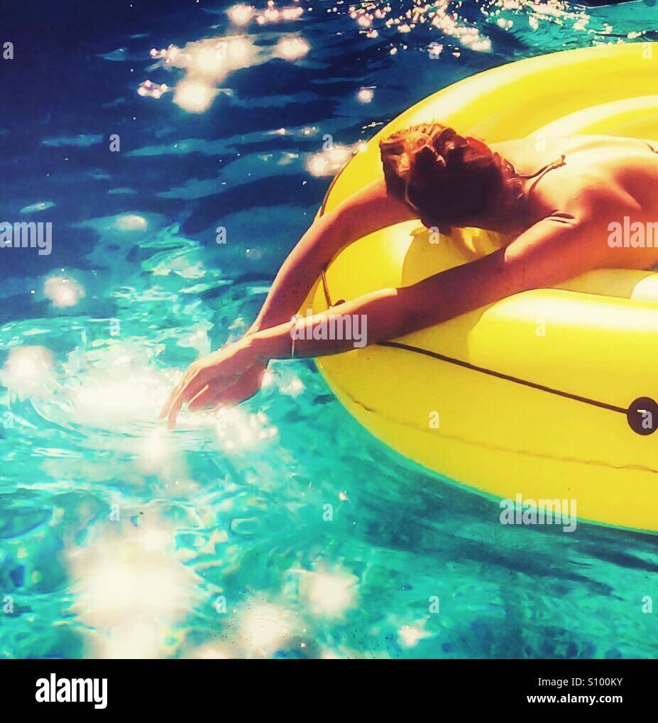 Donna rilassante in piscina dopo una calda giornata di sole. Immagini Stock