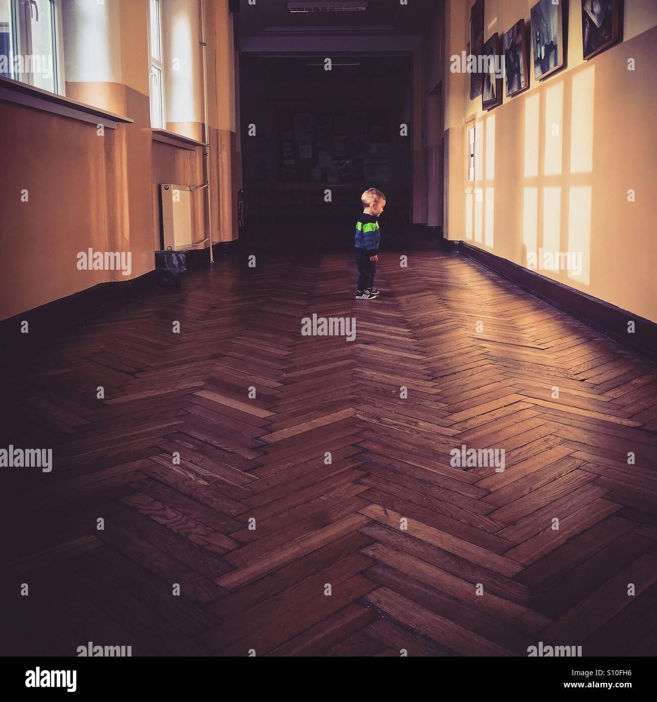 Baby boy in piedi in un lungo corridoio scuola guardando le ombre Immagini Stock
