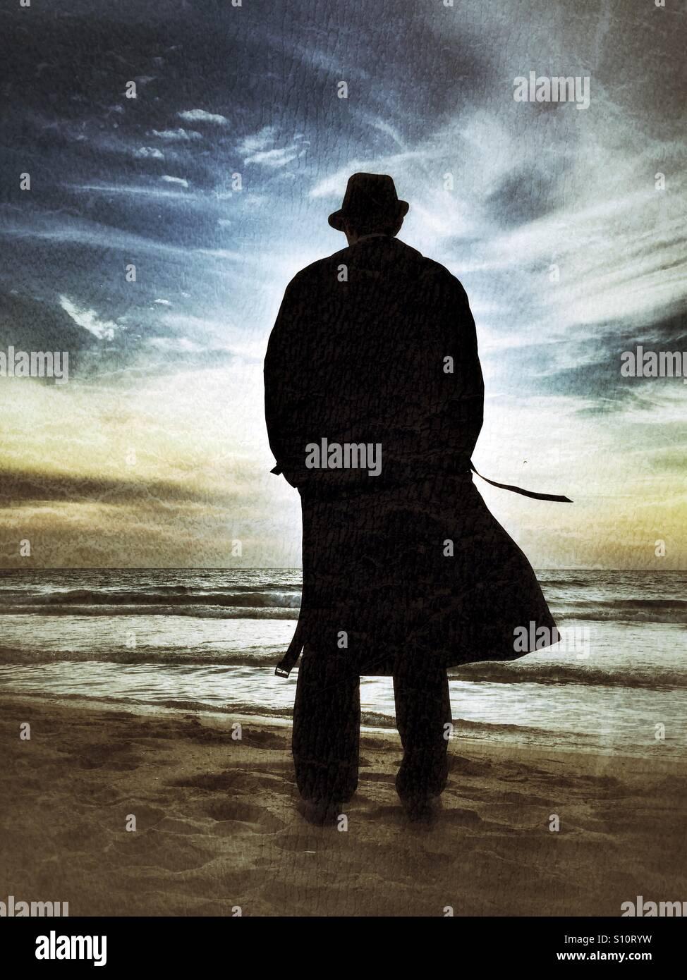 Uomo in un cappotto dal mare al tramonto Immagini Stock