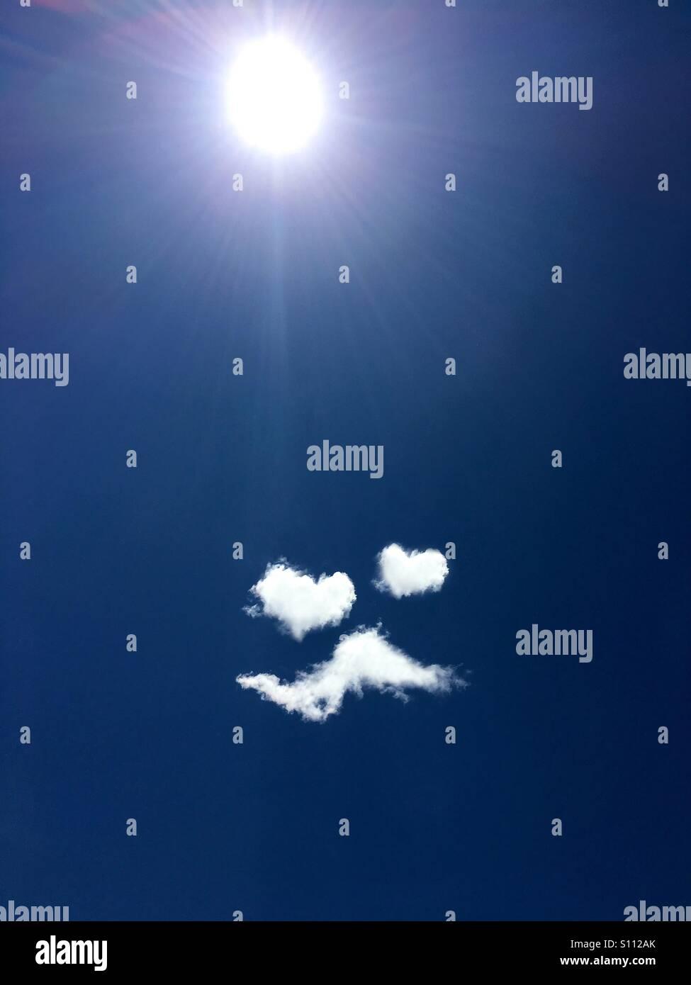 """Le nuvole formano un """"nell'amore"""" gli Emoji, con a forma di cuore di occhi e baffi Immagini Stock"""