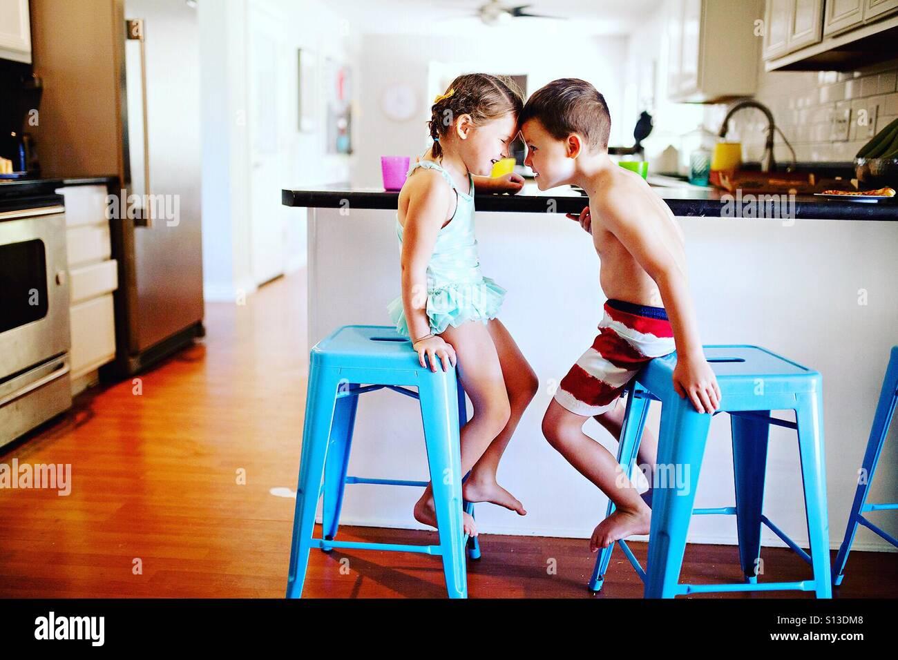 Due bambini in abiti nuotare essendo stupido al momento dei pasti a casa nella cucina moderna Immagini Stock