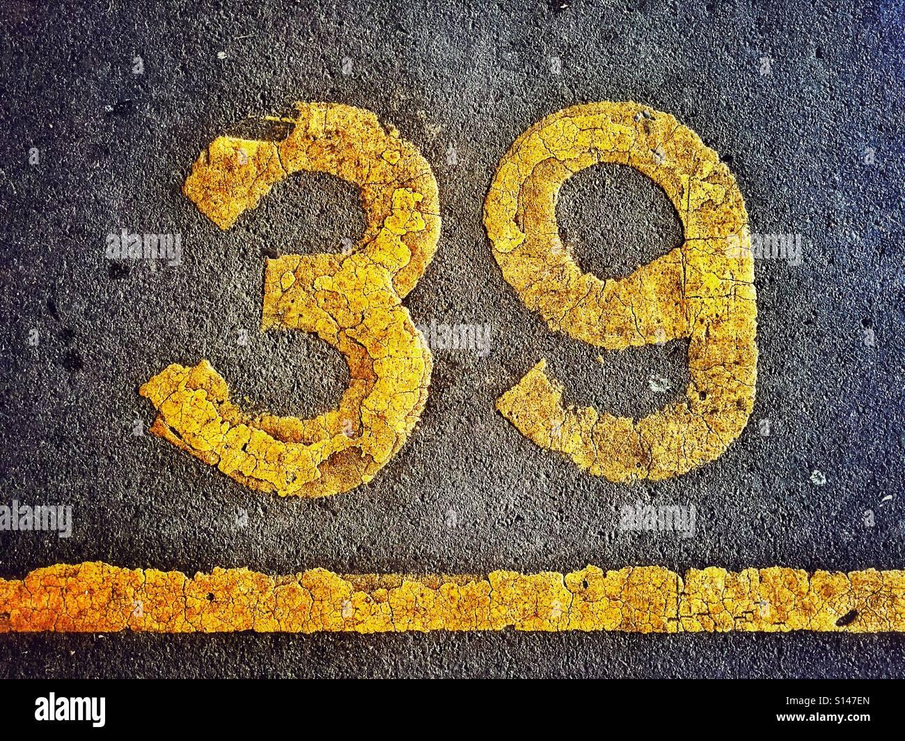 Il numero 39 è dipinta sulla superficie catramata di un parcheggio auto per identificare un particolare parcheggio Immagini Stock