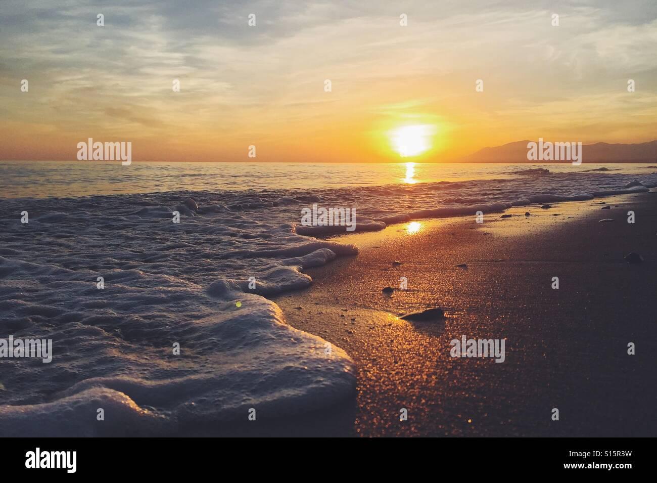 Tramonto su una spiaggia di sabbia con onde Immagini Stock