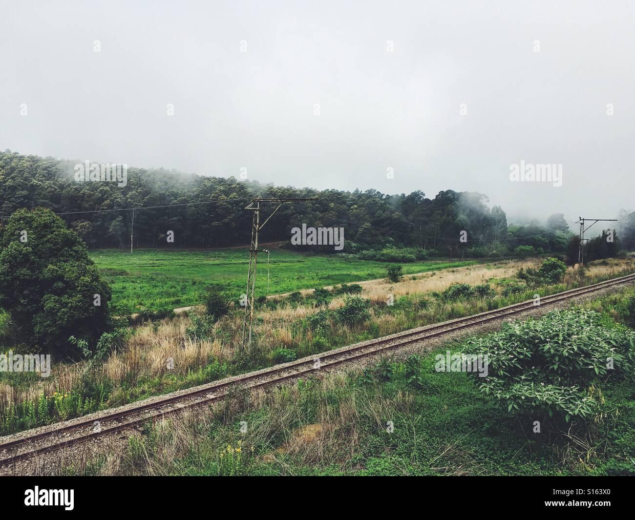 La laminazione di nebbia in oltre le linee ferroviarie nella tranquilla cittadina di piccole dimensioni Immagini Stock