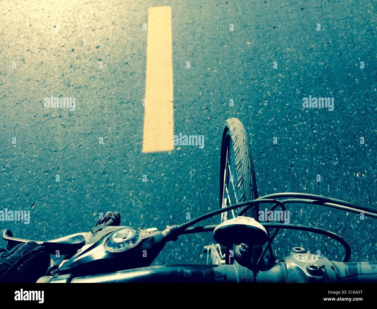 In sella ad una bicicletta su una strada asfaltata; vista dal manubrio Immagini Stock