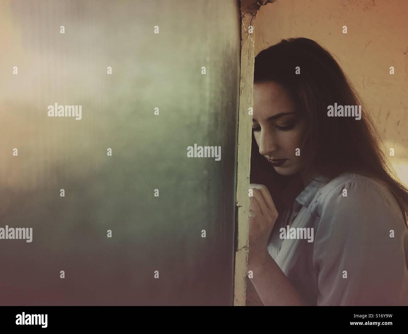 Triste donna mediante la finestra Immagini Stock