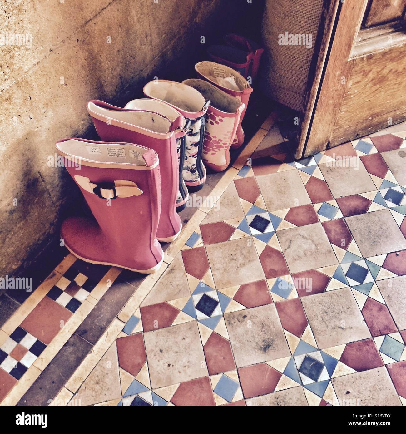 Una famiglia di stivali Wellington allineati alla porta in una casa di campagna - casa di famiglia - vita di campagna Foto Stock