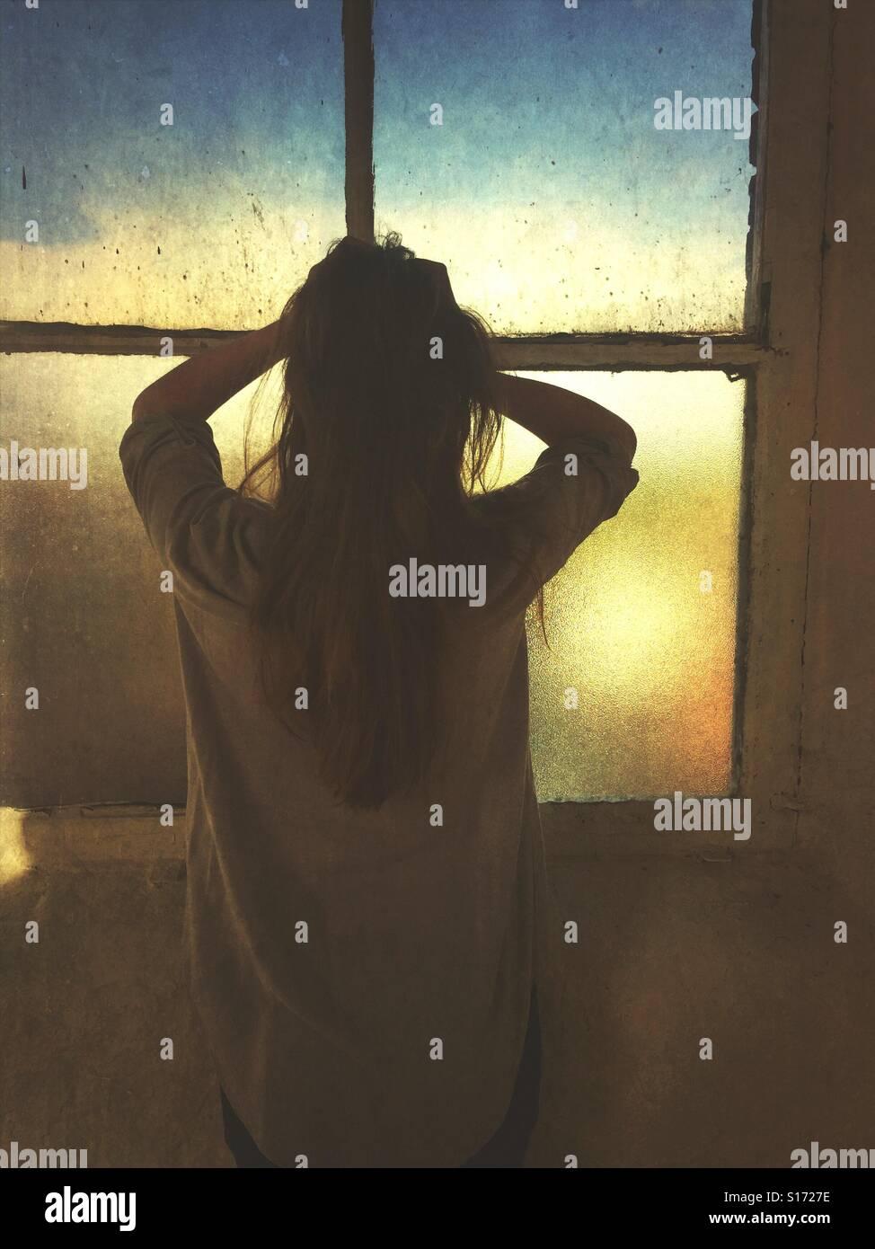 Vista posteriore di una donna ha sottolineato in testa le mani dalla finestra Immagini Stock