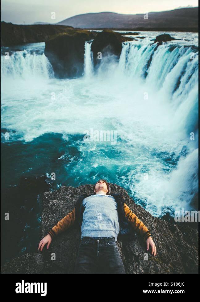 Un ragazzo guardando una cascata Foto Stock