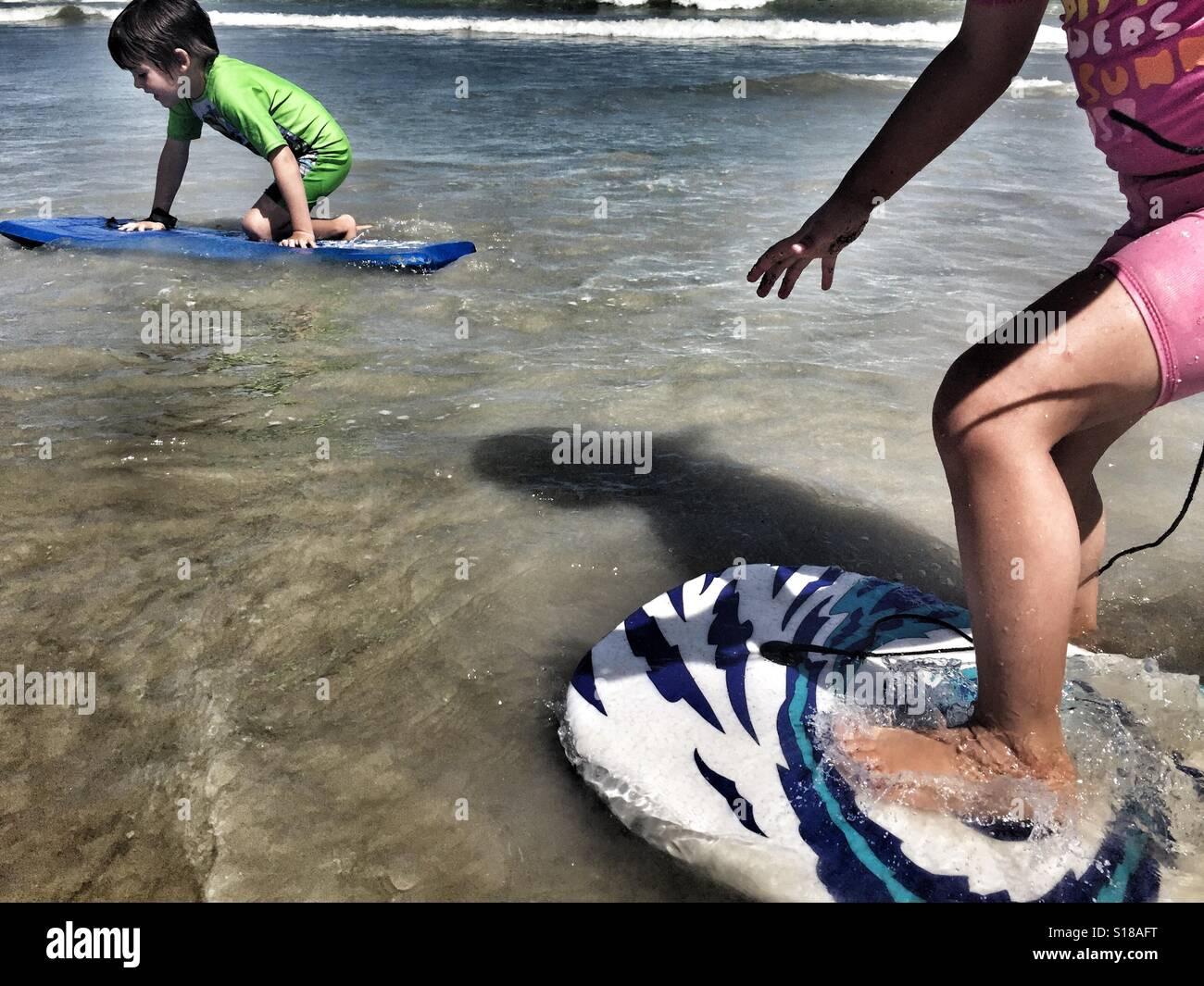 I bimbi a giocare con tavole boogie in mare Immagini Stock