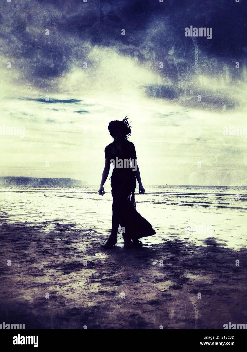 Misteriosa donna stagliano su una solitaria spiaggia. Immagini Stock