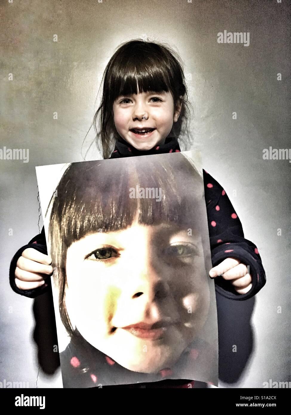 5 anni di ragazza con grande stampa fotografica di se stessa Foto Stock