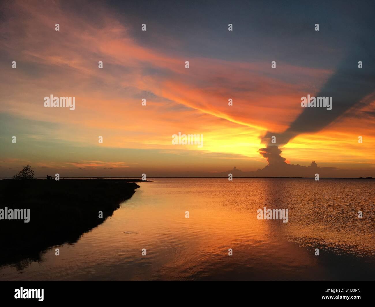 Cool tramonto sull'oceano. Il Cloud ombra. Profondi e saturi e caldi colori Offshore. Immagini Stock