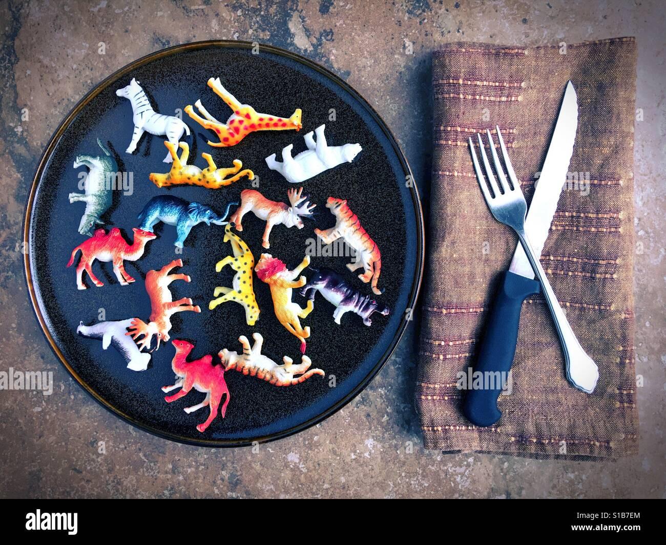 Giocattolo di plastica di animali su una piastra accanto a un coltello e forchetta. Immagini Stock