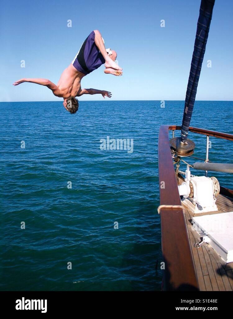 Un giovane uomo fa s backflip off la prua di una barca in mare. Immagini Stock