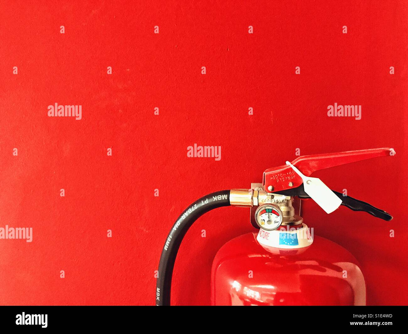 Estintore dettaglio contro uno sfondo rosso Immagini Stock