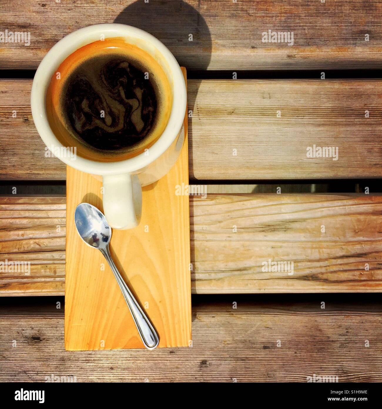 Un overhead shot di un americano e un cucchiaio in legno di un piatto di portata su una panca in legno Immagini Stock