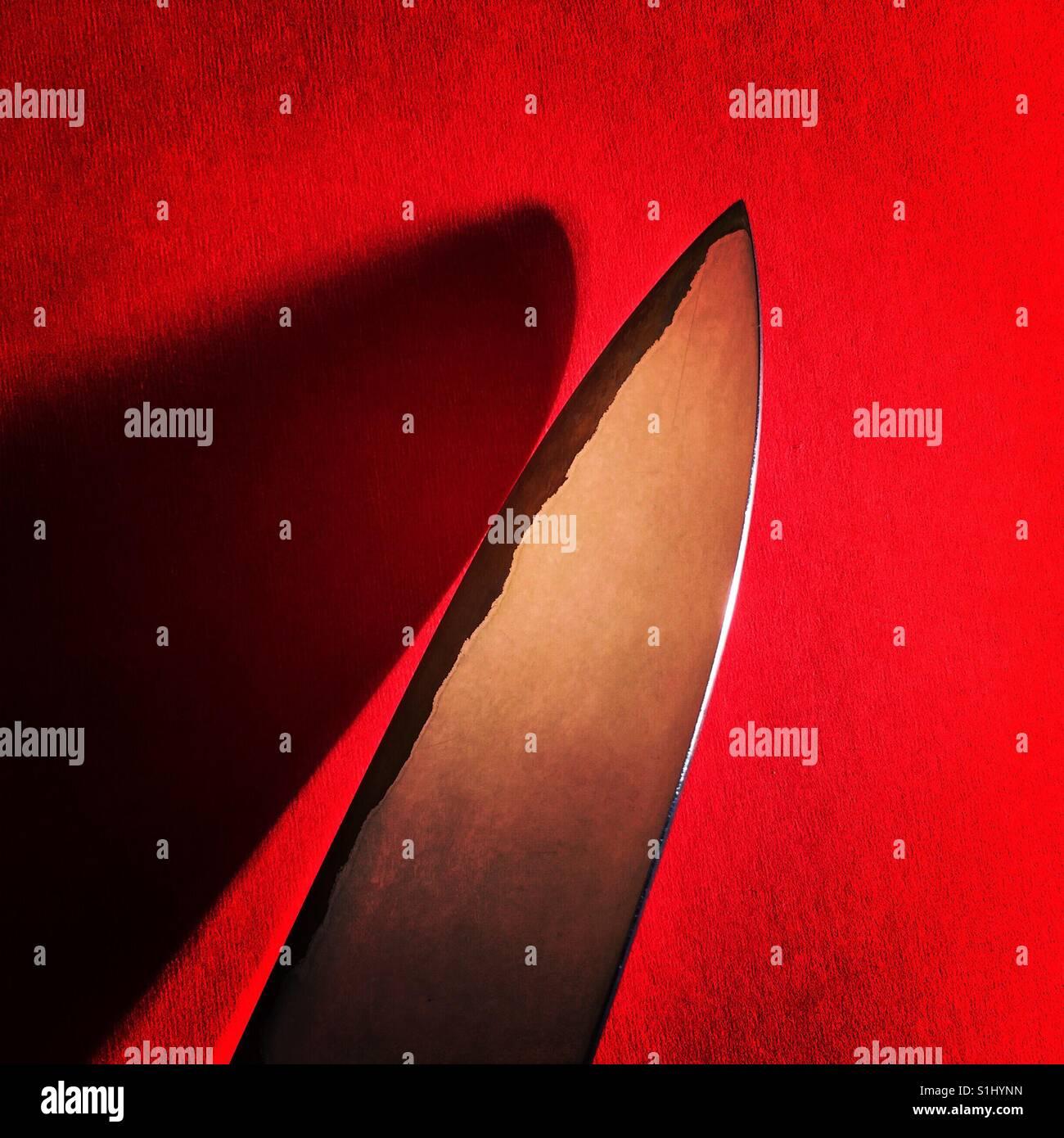 La lama di un coltello su una superficie di colore rosso con una profonda ombra Immagini Stock