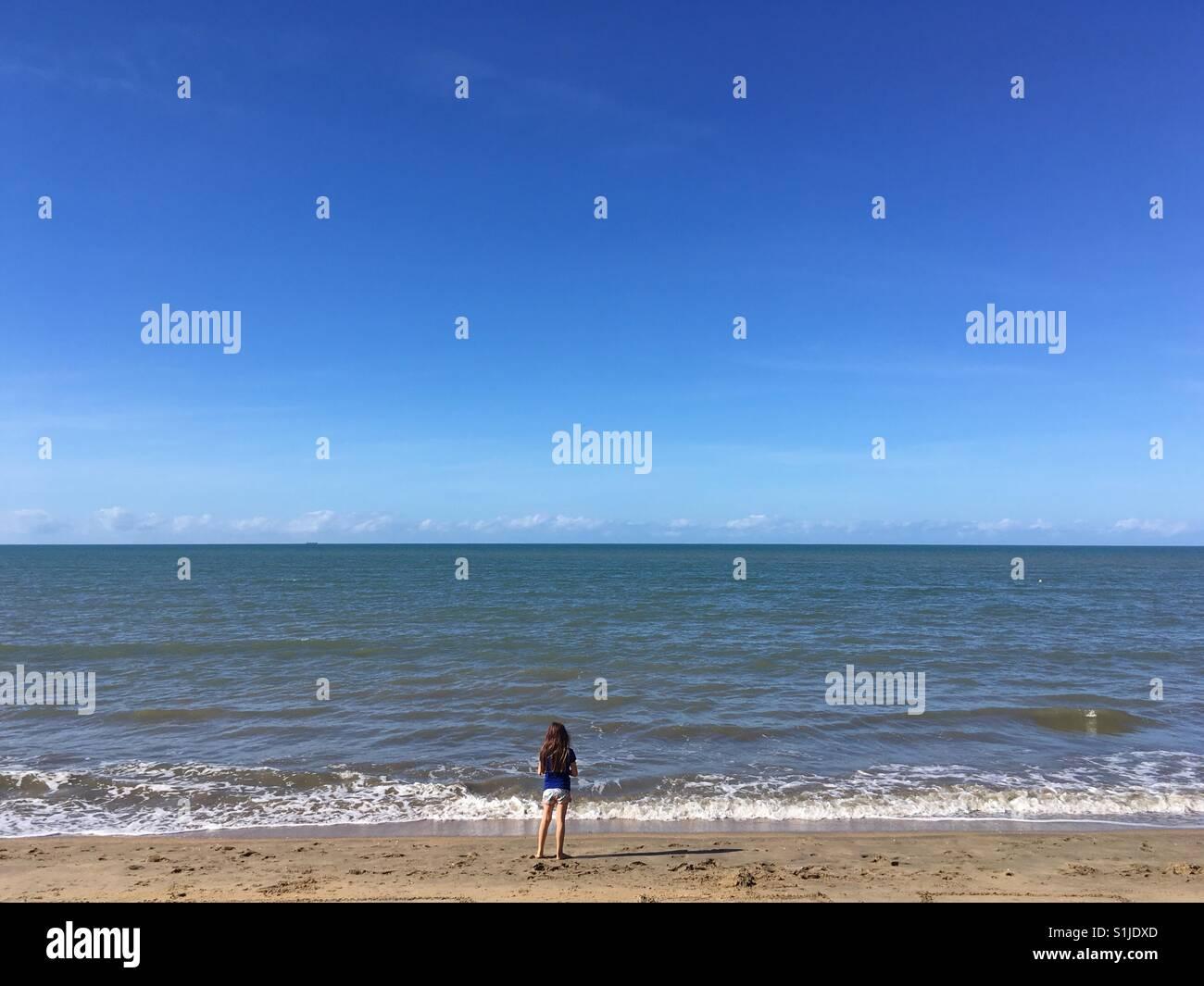 Bambina fissando l'orizzonte su una spiaggia. Immagini Stock