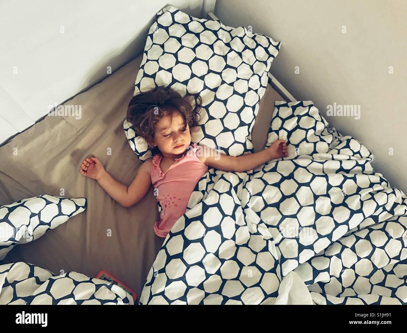 Ragazza Litttle dormire su un letto grande Immagini Stock