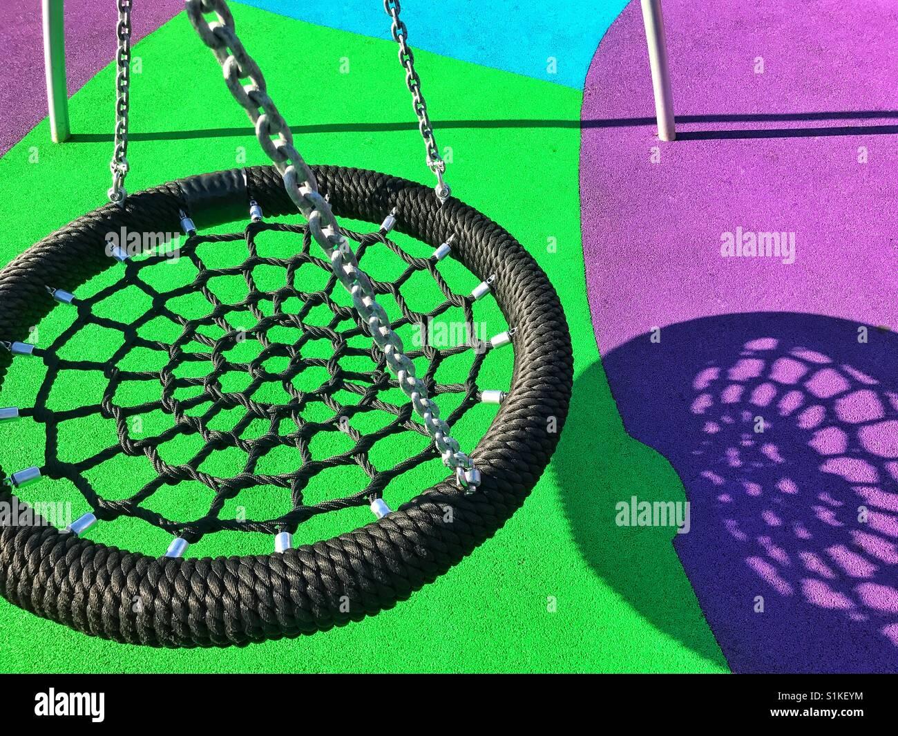 Un nuovo tipo di swing getta un ombra interessanti sulla terra colorata in un parco giochi per bambini. Una immagine Immagini Stock