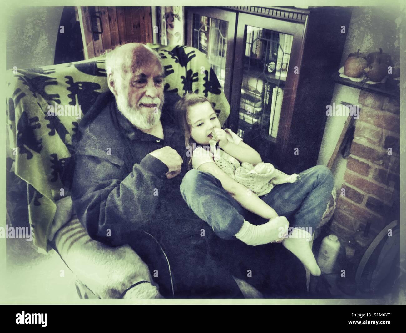 Coccole e TV con il nonno. Immagini Stock