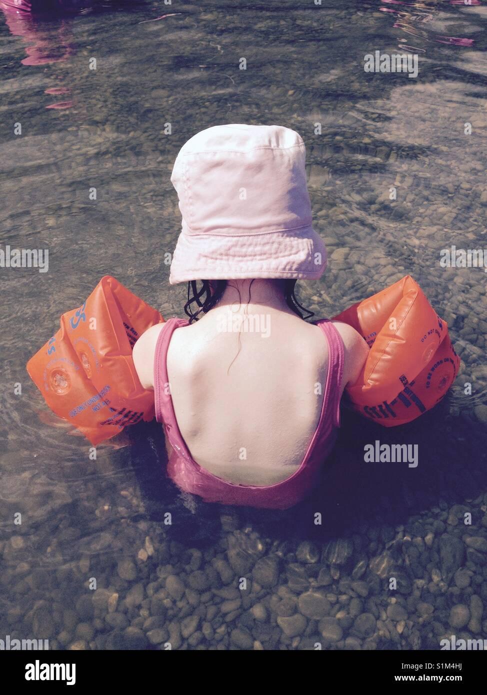 Giovane ragazza / toddler va nuoto con cappello per il sole e fasce da braccio Immagini Stock