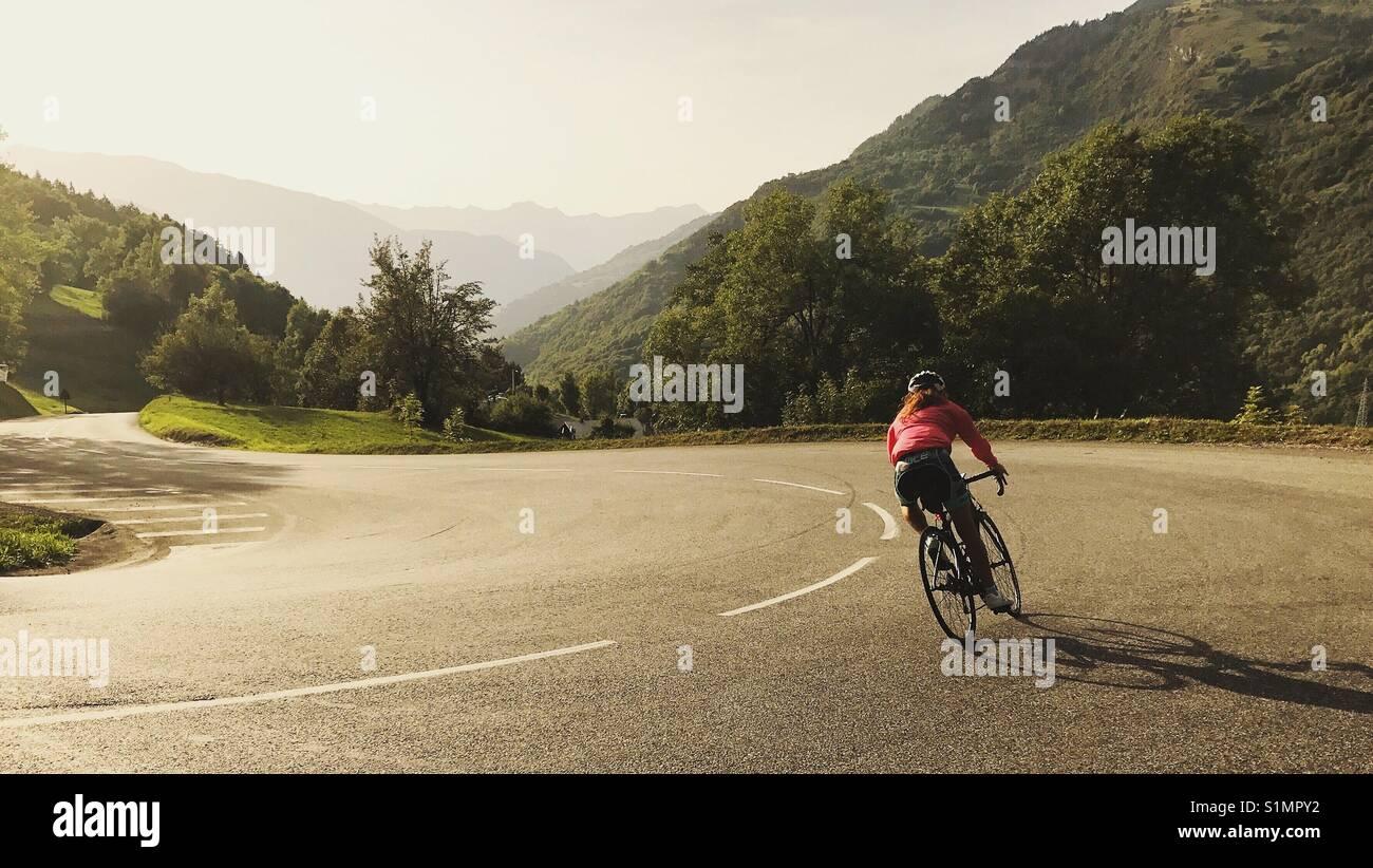 Donna in bicicletta scendendo una strada di montagna Immagini Stock