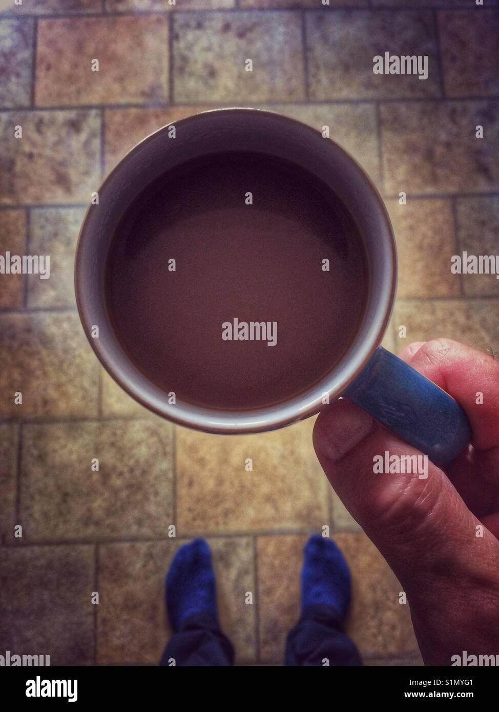 Un punto di vista shot guardando verso il basso su una tazza di tè o caffè che viene sollevato fino a Immagini Stock