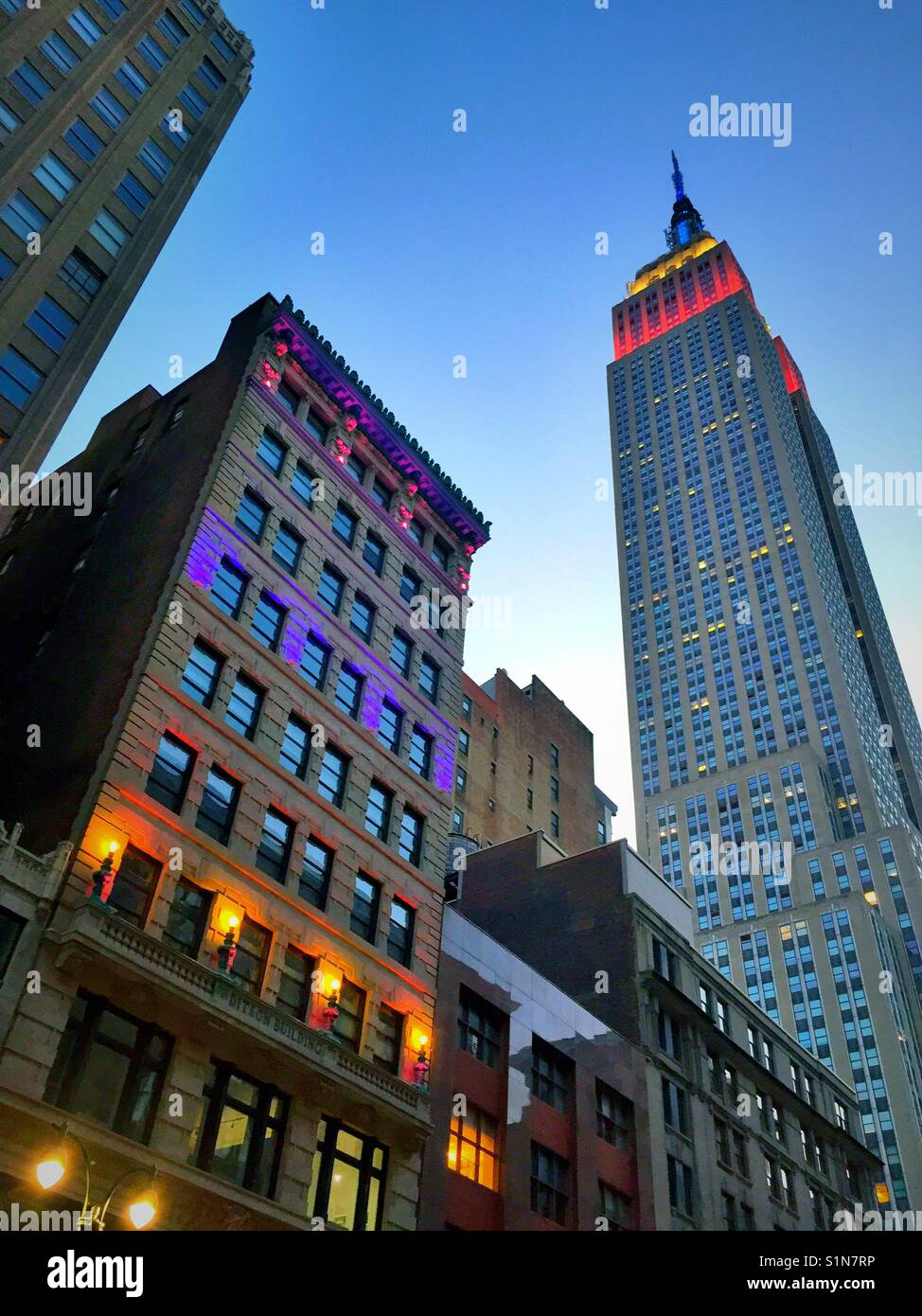 La città di New York al crepuscolo con il luminoso edificio Ditson e Empire State Building, Midtown Manhattan, USAA Foto Stock