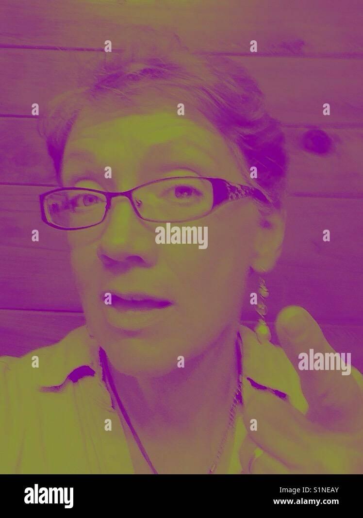 La realizzazione di un punto in viola e verde- donna matura punti il dito Immagini Stock