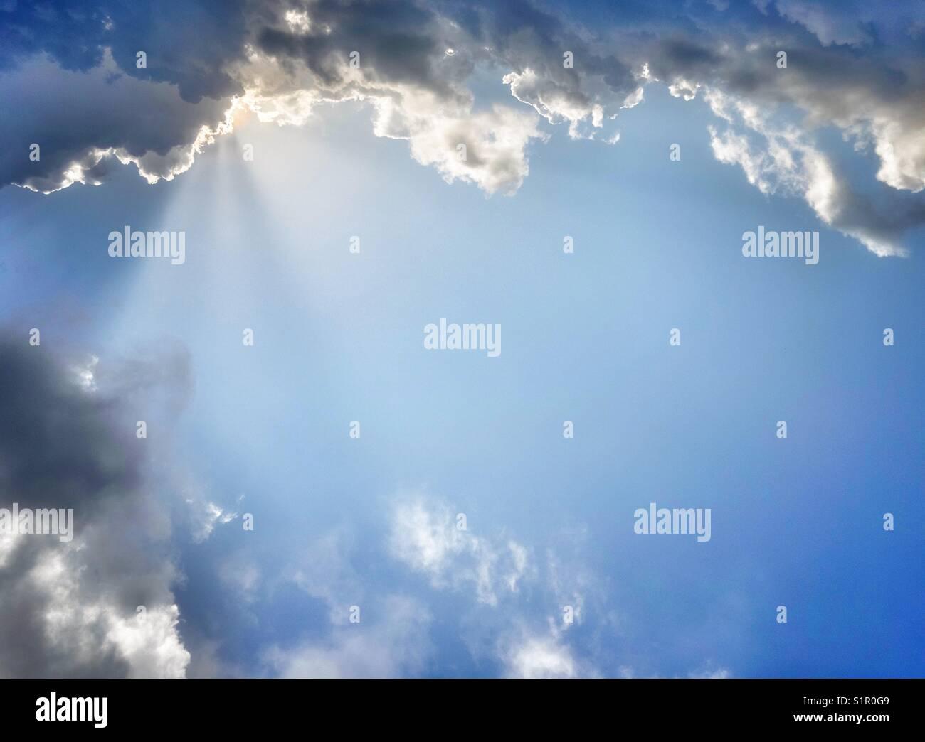 Sole che splende attraverso le nuvole. Immagini Stock