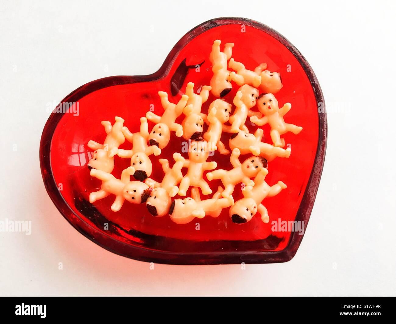Giocattolo di plastica dei neonati in un cuore piatto sagomato. Immagini Stock