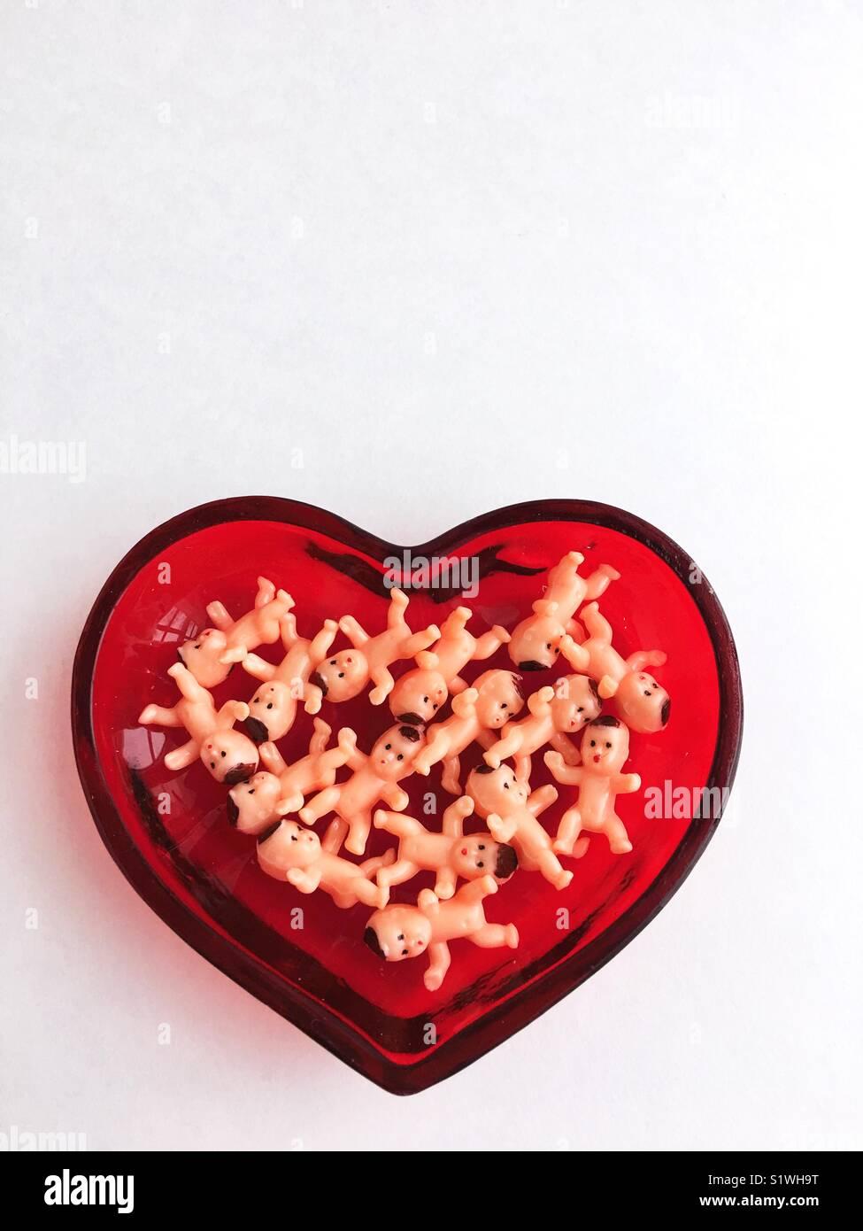 Giocattolo di plastica baby dolls in un cuore piatto sagomato. Immagini Stock