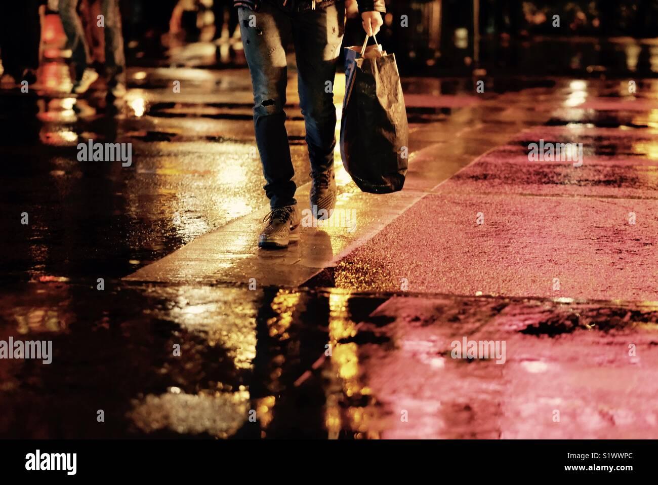 Shopper attraversando il pavimento bagnato di notte Immagini Stock