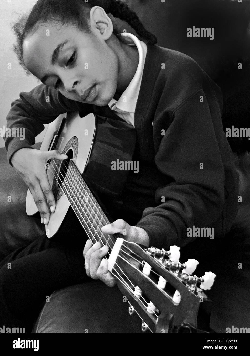 Una giovane ragazza di suonare una chitarra. Immagini Stock