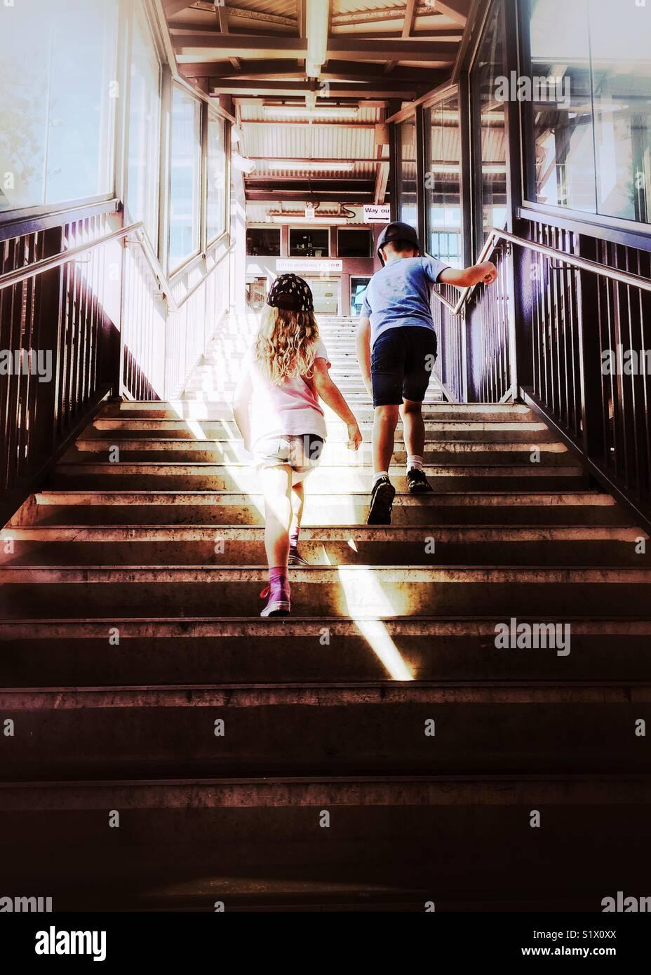 Due bambini salire le scale alla stazione ferroviaria. Ragazzo e ragazza camminare fino a scala attraverso sunbeam Immagini Stock
