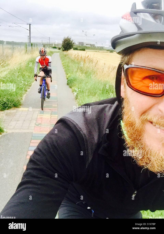 L uomo e la donna in bicicletta lungo un percorso di ciclo in Inghilterra Immagini Stock