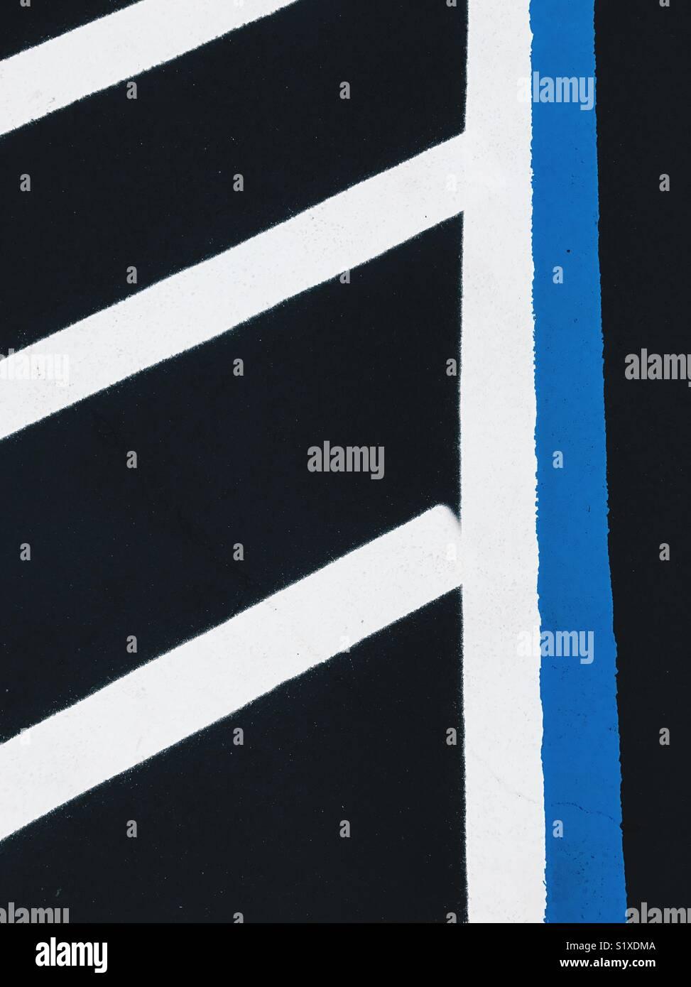 Bold dipinte di bianco e linee blu su asfalto nero in un parcheggio. Immagini Stock